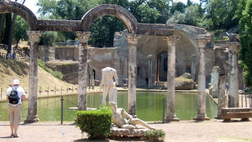 Person walking amongst ancient statues and architecture in Tivoli