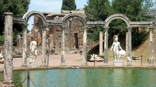 Pool surrounded by sculptures and ruins in Tivoli