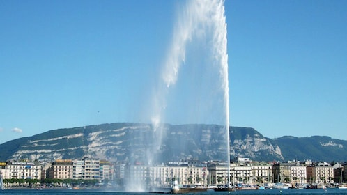 View of city with water jet from boat spraying into the air in Geneva