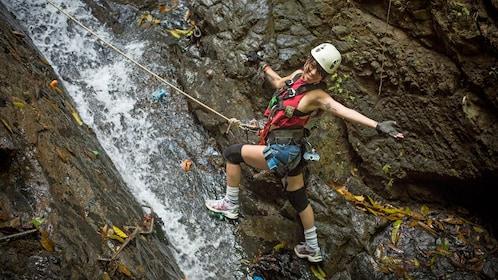 woman in gear climbing up a waterfall in Costa Rica