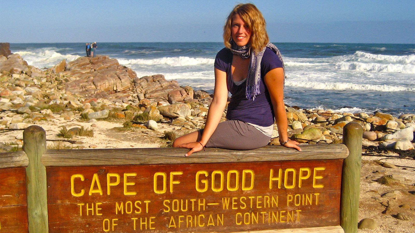 Woman taking a photo with the Cape of Good Hope sign in South Africa