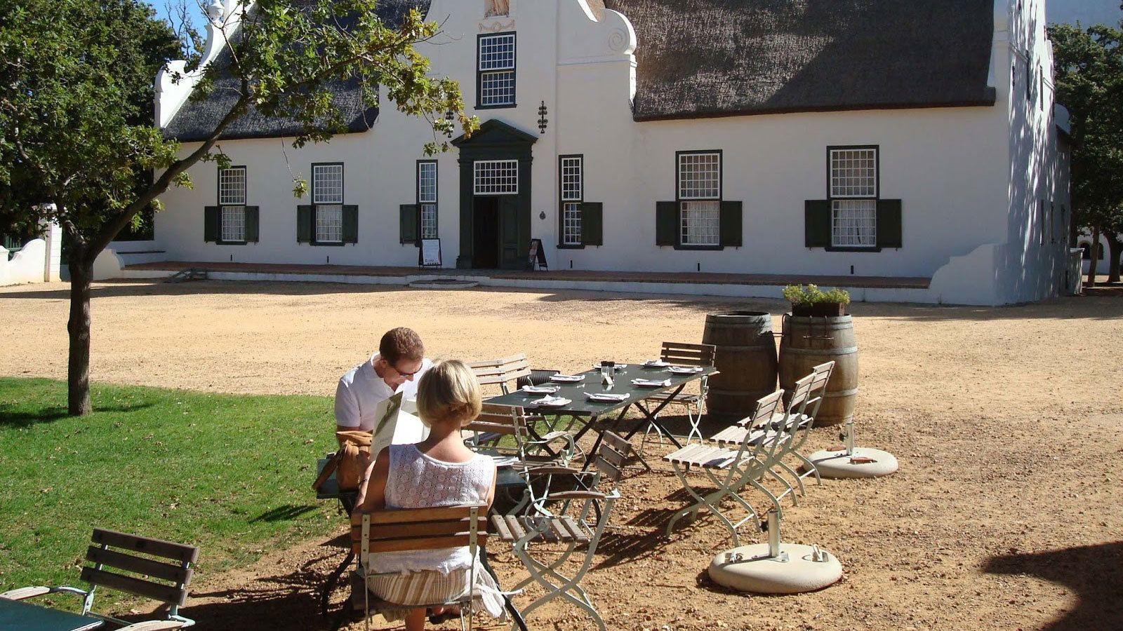 Couple sitting at a table outside a vineyard in Cape Town