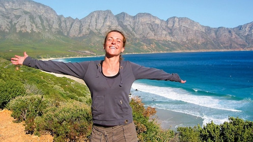 Woman holding out her arms standing on the coast in Cape Town