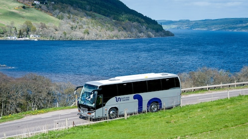 Tour bus on a narrow road along the water in Inverness