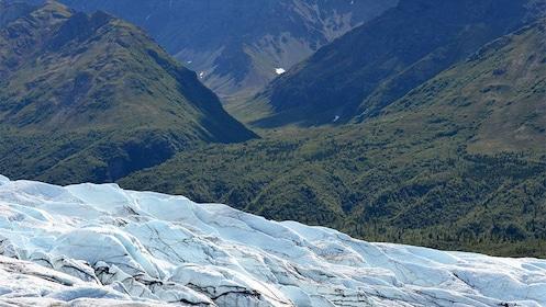 Glacier next to green hills