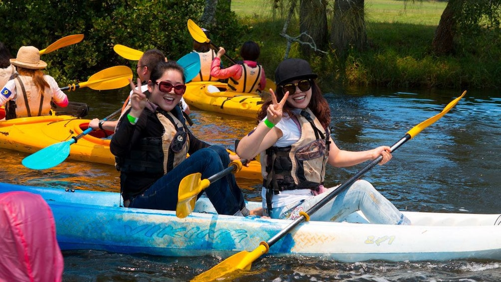 Show item 3 of 4. Pair of women kayaking with group in Sydney