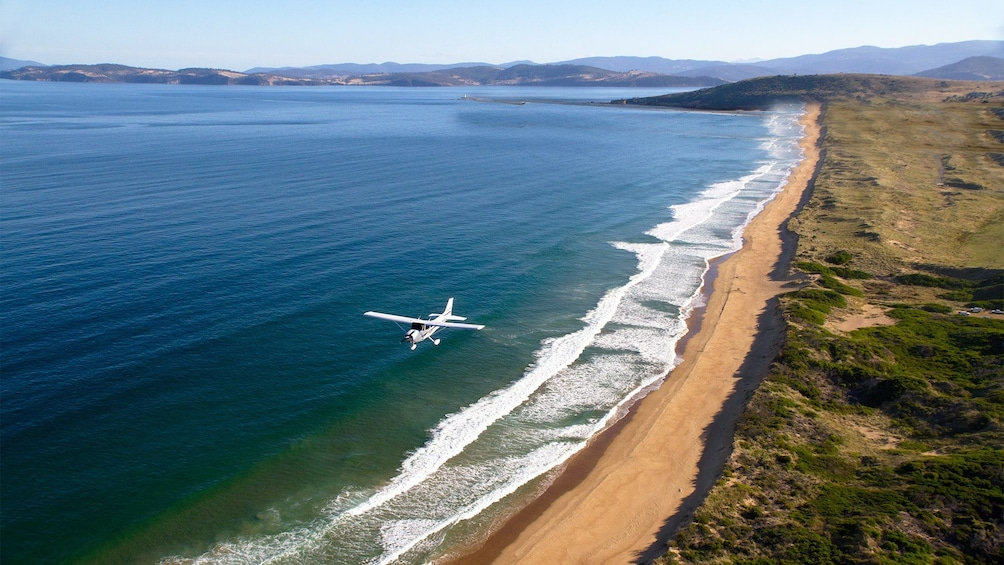 Show item 4 of 5. Aerial view of the plane flying above the waters on the Learn to Fly Discovery Package at Par Avion Wilderness Tours in Hobart and Surrounds, TAS, Australia