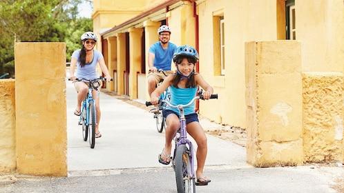 Family of three ride bikes
