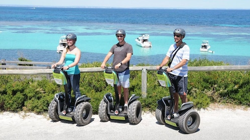 Three people on Segway scooters near the beach