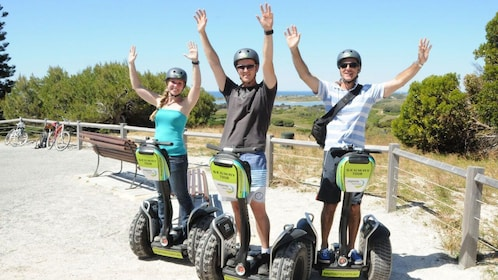 Three people on Segway scooters near the beach hold their arms up