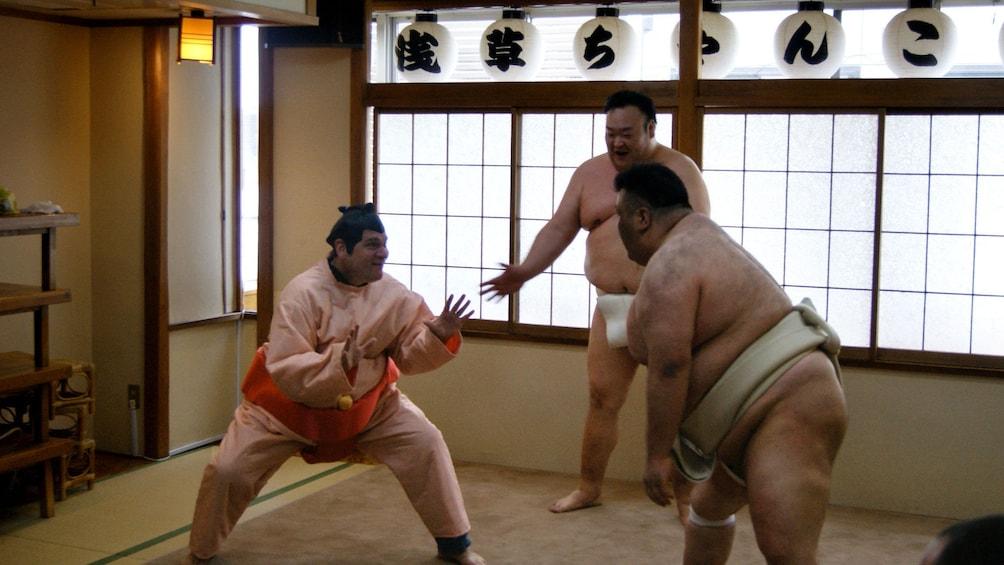 Show item 1 of 7. Man in sumo costume challenging a sumo wrestler in Tokyo