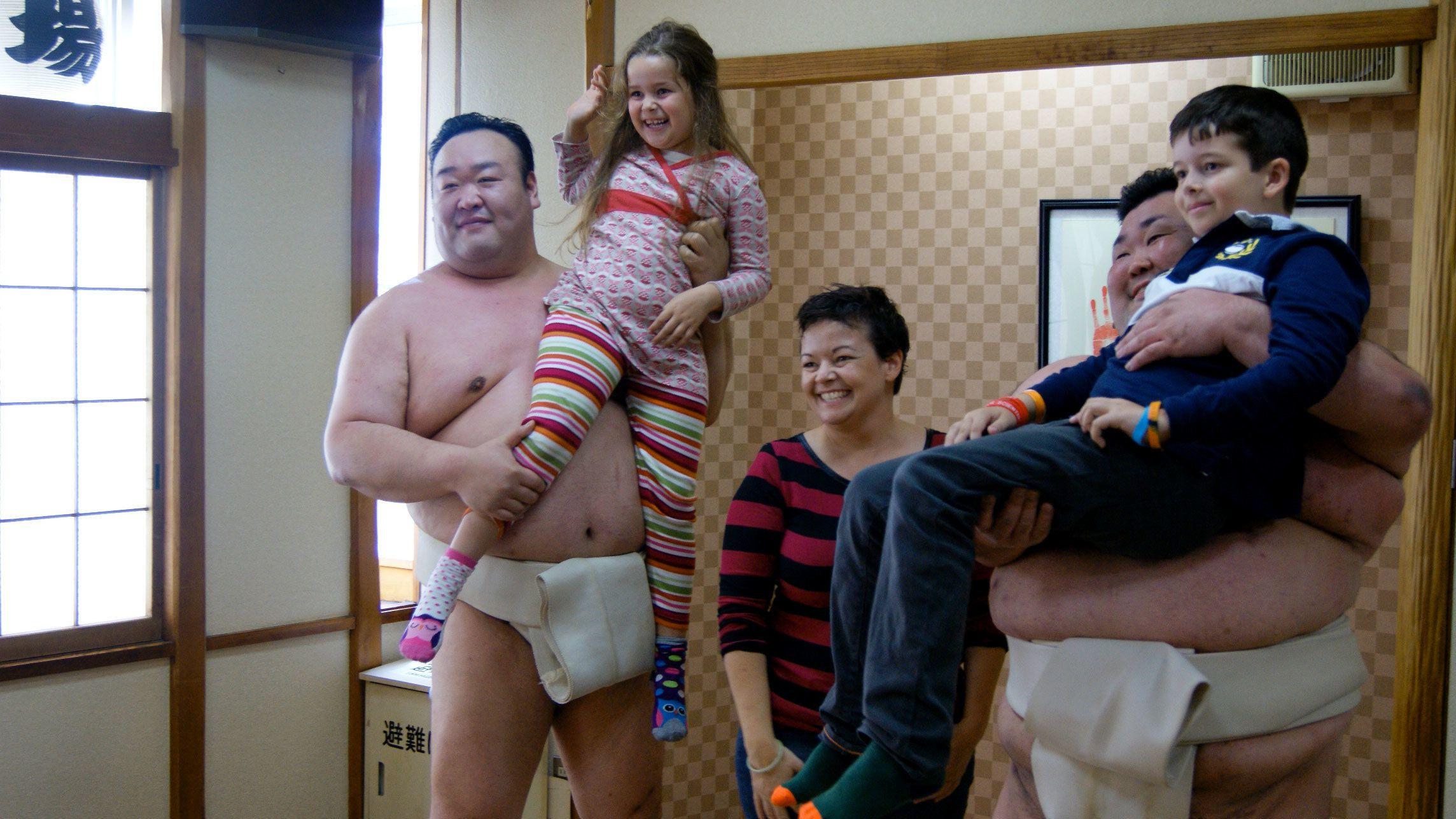 Sumo wrestlers holding children in Tokyo