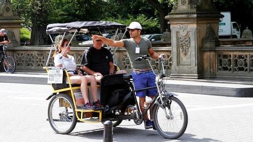 Pedicab driver describing sites to passengers in Central Park