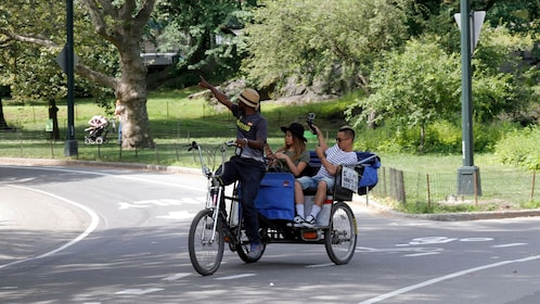 Pedicab driver pointing out sites to passengers in Central Park