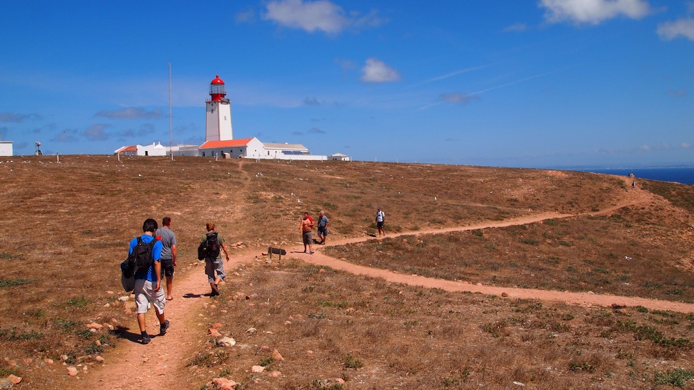 People walking on a path towards a lighthouse on Berlengas Islands