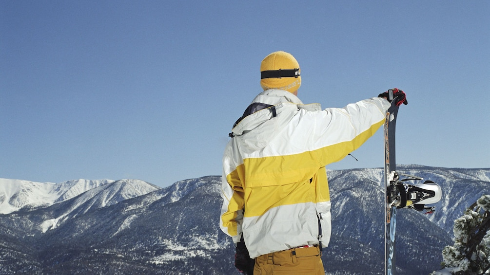Cargar ítem 1 de 10. Snowboarding man looking out at the view in Colorado