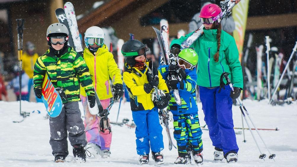 Cargar ítem 4 de 5. Group carrying rented skis
