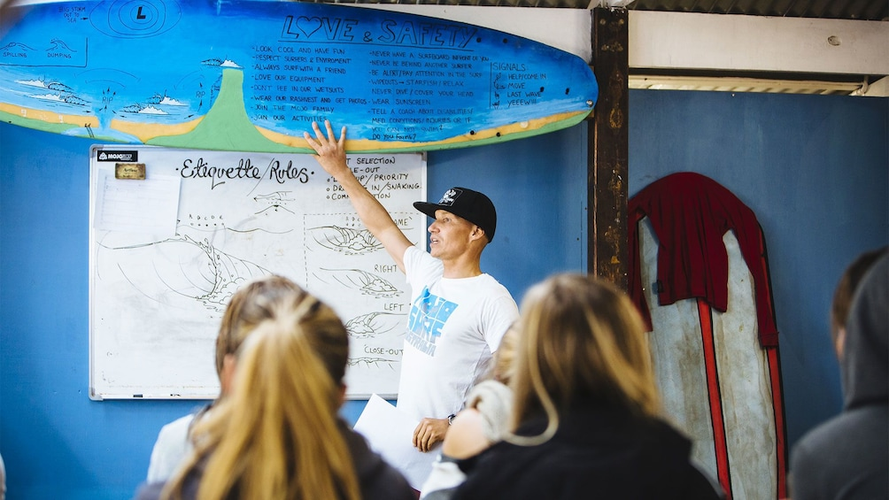 Show item 3 of 4. Group receiving instruction on the Byron Bay Surf Lesson in Australia