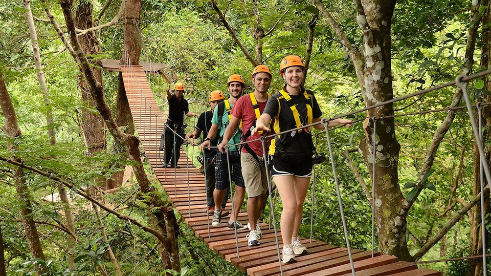 Show item 3 of 5. Group crossing a bridge on the Flying Hanuman Course in Phuket