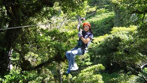 Woman ziplining through the trees in Costa Rica