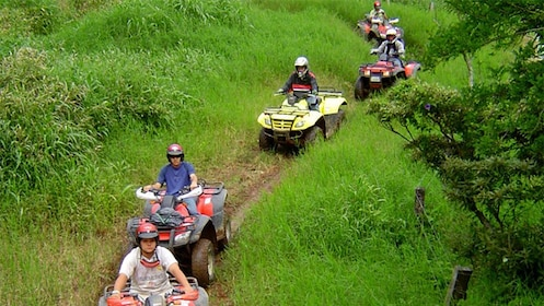 Line of ATV riders on a path through the grass in Costa Rica