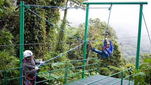 Ziplining woman slowing to a stop in Costa Rica