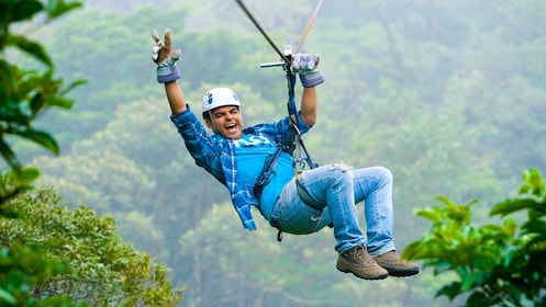Man flashing a peace sign while ziplining in Costa Rica