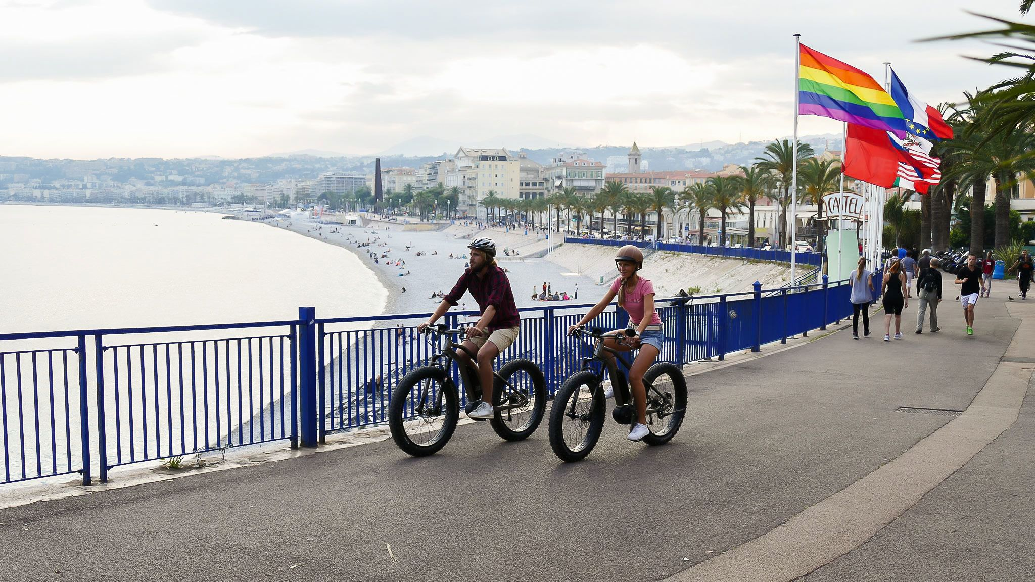 Couple riding bicycles along the boardwalk at the French Riviera