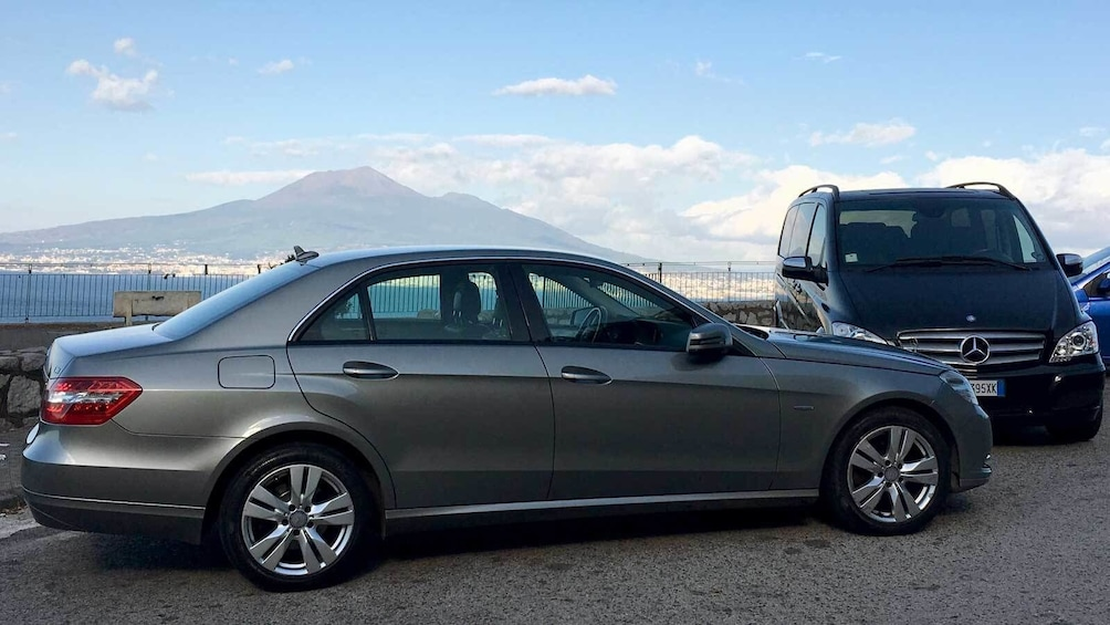 Sedan on the road with Mount Vesuvius in the background