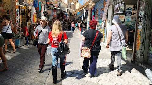 Tour guide and group on a market street in Athens