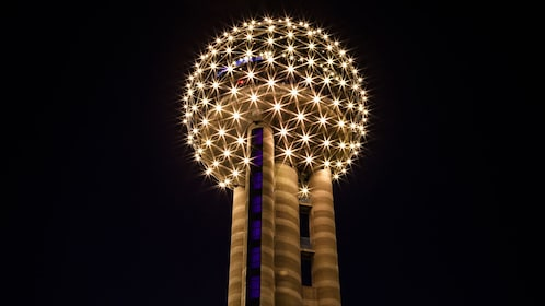 circular structure lit at the top of a tower in Dallas