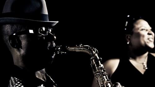 Man playing saxophone next to smiling woman