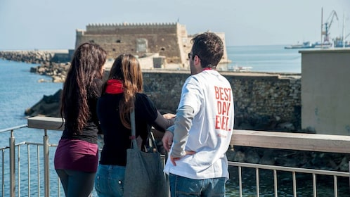 Tour guide with pair of women looking out at buildings along the water in Heraklion