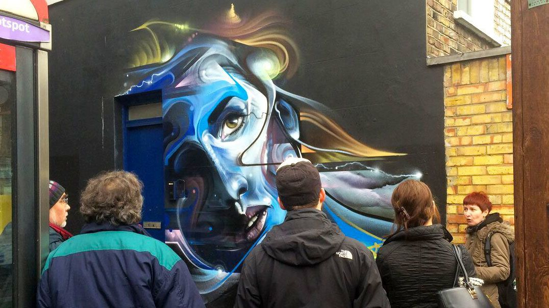 Tour group looking at colorful street art in London