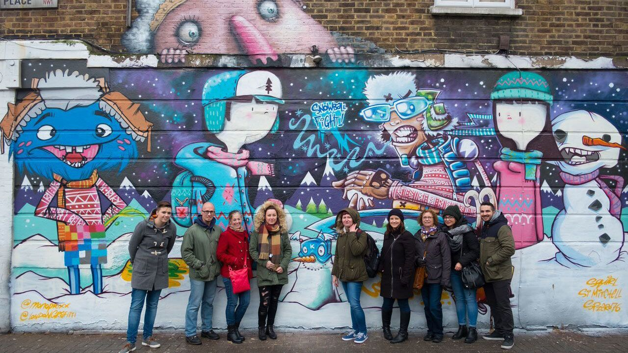 Tour group in front of a large wall of graffiti in London