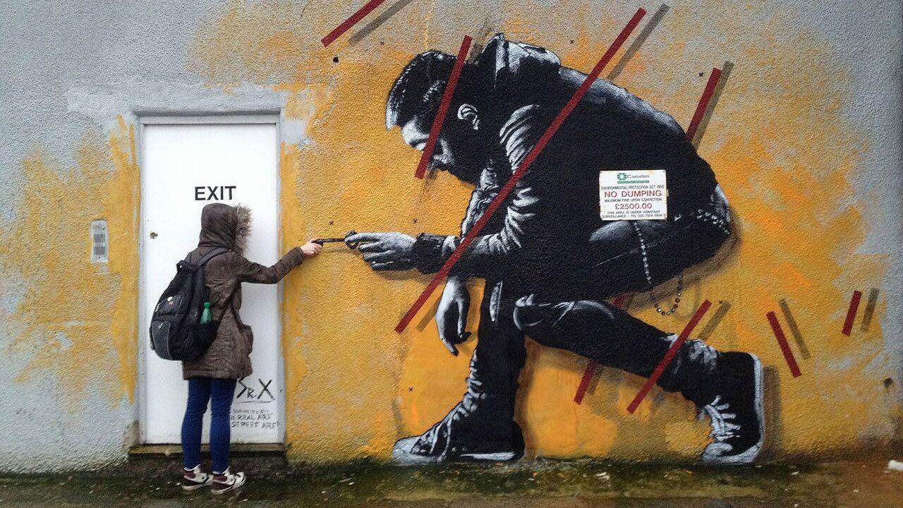 Woman posing with graffiti mural in London