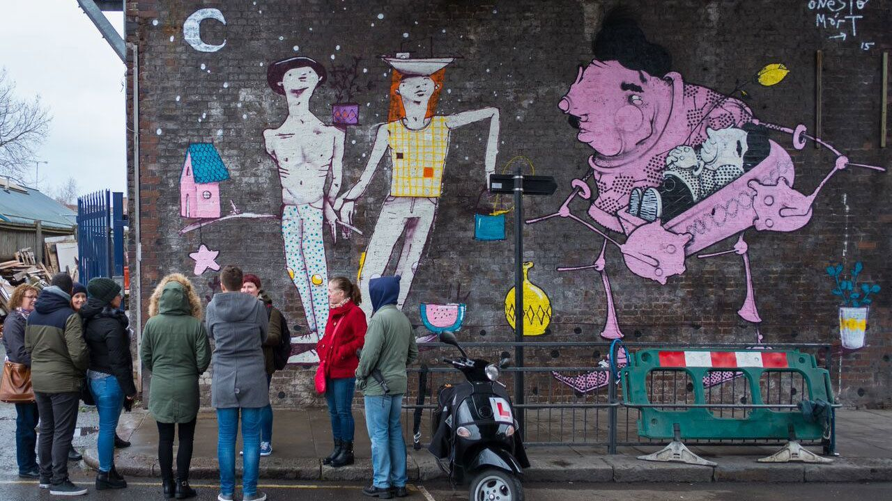 Tour guide and group looking at large scale street art on a wall in London