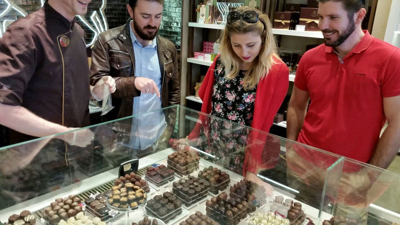 Group looking at display of chocolates in a shop in London