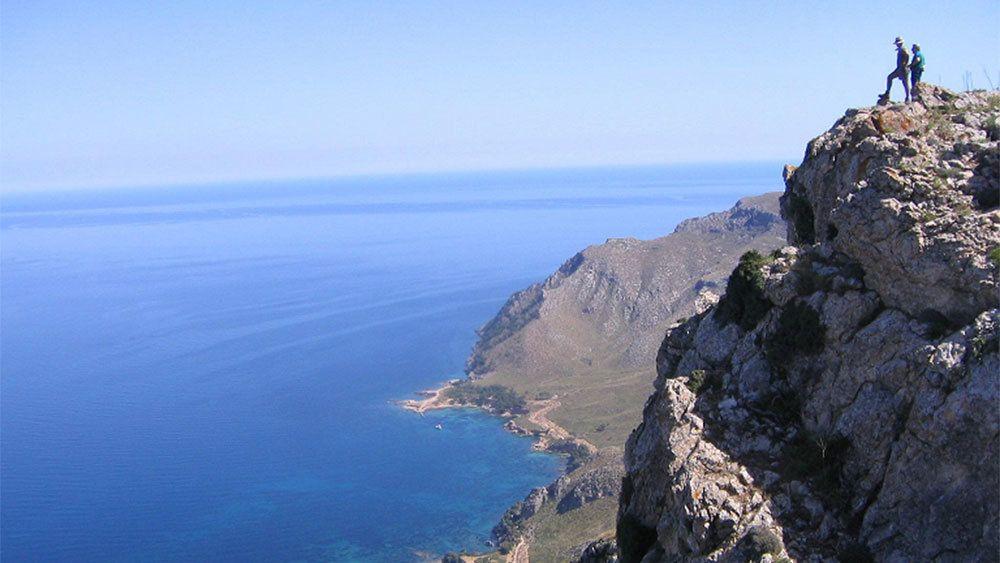 Hikers on the edge of a coastal cliff on Mallorca Island