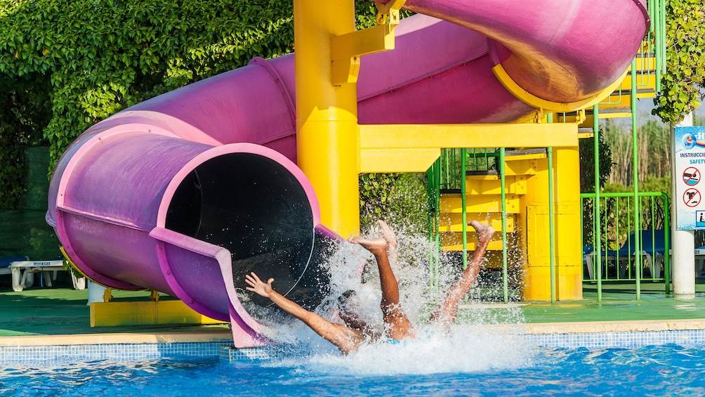 A man going down a water slide at hidropark alcudia