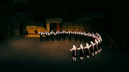 Dancers in a half-circle formation onstage in AThens