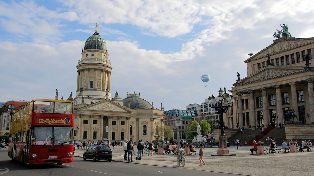 Hop-on hop-off bus driving past historic buildings in Berlin