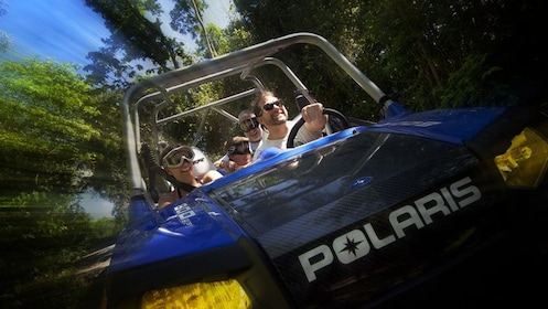 People riding in Polaris off road vehicle in Cancun