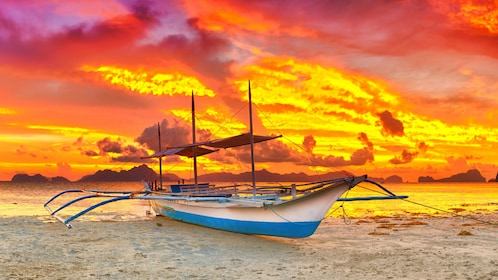 Boat on beach with dramatic sunset in background