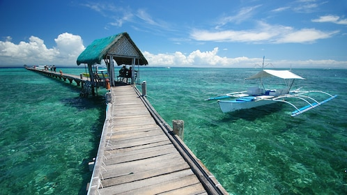 Boardwalk over the water with boat on the ready in Cebu Island.