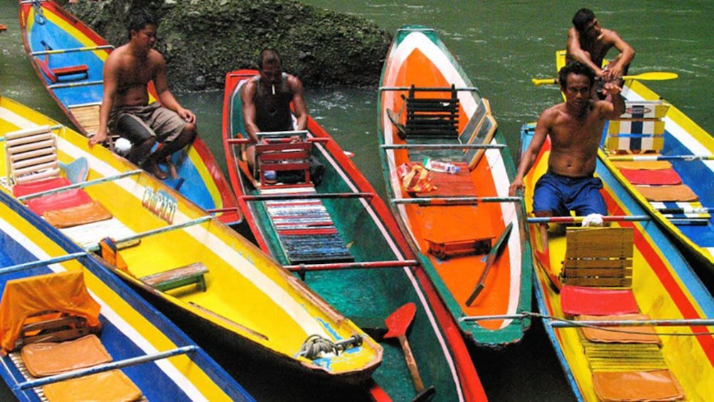 Show item 4 of 5. Men in colorful canoes