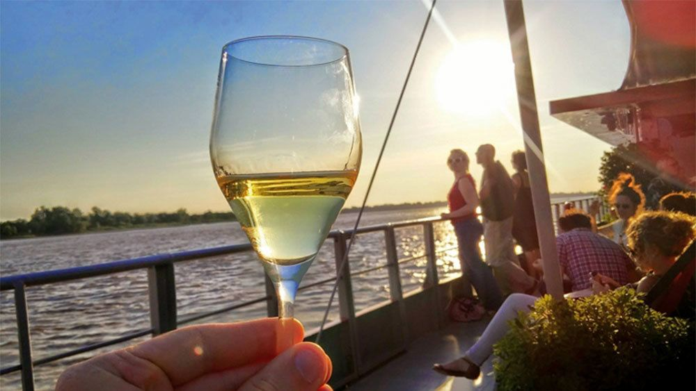 Boating passenger with glass of white wine in Bordeaux