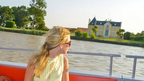Woman looking out at the scenery from the deck of a boat in Bordeaux