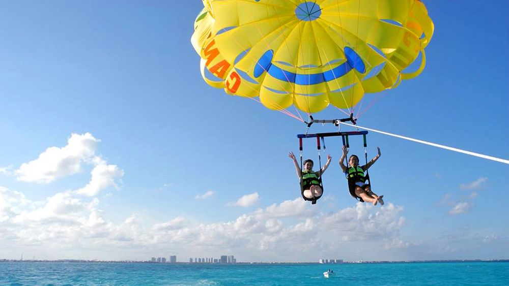 friends having fun parasailing in Cancun