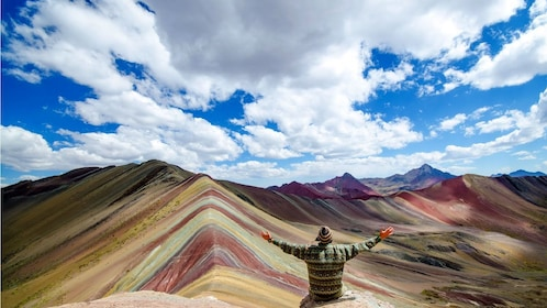 Hiking man sitting on a rock looking out at the colorful peaks of Rainbow Mountain in Lima